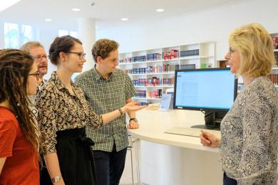 Gruppe von Benutzerinnen und Benutzern steht bei einer Benutzungseinführung im Lesesaal um einen Katalogbildschirm herum