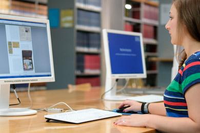 Eine Benutzerin liest eine Netzpublikation an einem unserer Leseesaal-PCs. Im Hintergrund Bibliotheksregale mit Büchern.