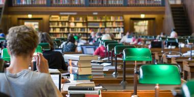 Ein Benutzer im geisteswissenschaftlichen Lesesaal der Deutschen Nationalbibliothek in Leipzig vor einem Stapel Bücher und seinem Notebook