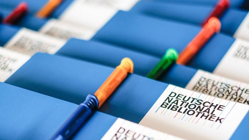 Tagungsmappen und Kugelschreiber mit einem Aufdruck der Deutschen Nationalbibliothek