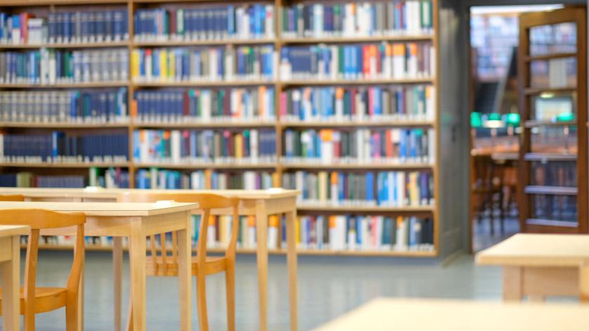 Bücherregale, Tische und Stühle im Lesesaal einer Bibliothek