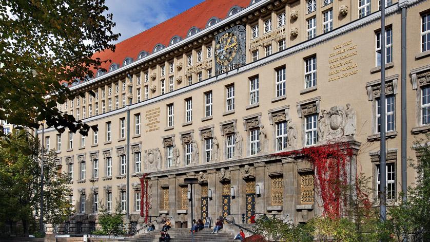 Fassade des historischen Gründungsbaus der Deutschen Nationalbibliothek in Leipzig mit Treppe zum Portal im spätsommerlichen Licht. Menschen sitzen auf der Treppe, rotgefärbtes Weinlaub umrankt die Seiten des Eingangs