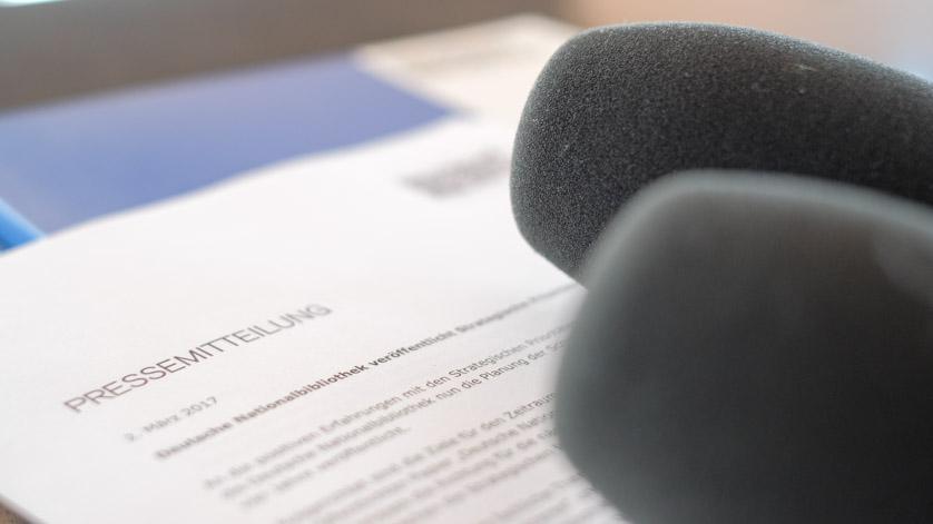 Pressemappe, Pressemitteilung und Mikrofone für eine Pressekonferenz