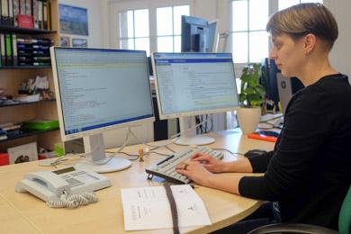 """Eine Mitarbeiterin der Deutschen Nationalbibliothek in Leipzig bei der PC-gestützten Katalogisierung eines Buches; der zweite Bildschirm gewährt ihr ständigen Einblick in das Toolkit des Regelwerks """"Resource Descripton and Access"""""""