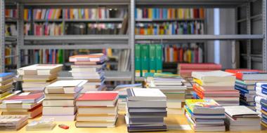Sortiertisch mit Bücherstapeln, im Hintergrund teilweise gefüllte Bücherregale
