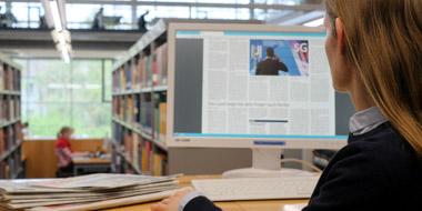 Im Lesesaal der Deutschen Nationalbibliothek liest eine Benutzerin auf dem Computerbildschirm die E-Paper-Ausgabe einer Tageszeitung. Auf dem Tisch liegen einige gedruckte Zeitungsausgaben.
