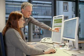 Ein Ausbilder gibt einer Studentin am Computermonitor Erläuterungen