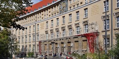 Fassade des historischen Gründungsbaus der Deutschen Nationalbibliothek in Leipzig mit Treppe zum Portal im spätsommerlichen Licht. Menschen sitzen auf der Treppe , rotgefärbtes Weinlaub umrankt die Seiten des Eingangs